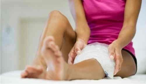 девушка прикладывает ледяной компресс к ноге
