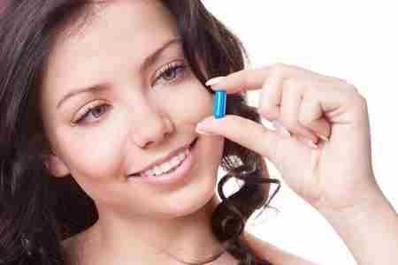 Женщина держит капсулы в пальцах